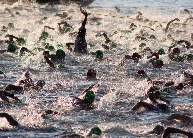 """US Navy 051015-N-9419C-004 Almost 2,000 triathletes begin the 2.4-mile swim at the Ironman World Championship triathlon, held in Kailua-Kona, Hawaii"" by U.S. Navy photo by Chief Journalist Deborah Carson - This Image was released by the United States Navy with the ID 051015-N-9419C-004 (next).This tag does not indicate the copyright status of the attached work. A normal copyright tag is still required. See Commons:Licensing for more information.বাংলা 